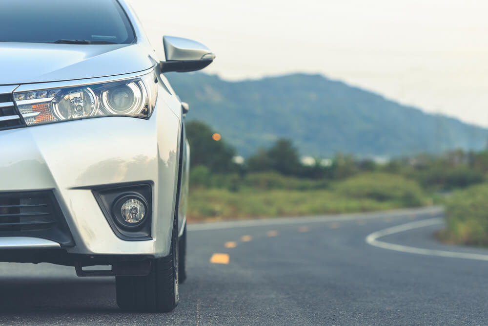 Auto Insurance: Fiction or Fact: Close up front of new silver car parking on the asphalt road